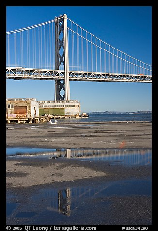 Bay Bridge reflected in water puddles. San Francisco, California, USA (color)