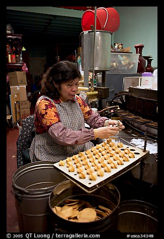 Woman folding fortune cookies, Chinatown. San Francisco, California, USA (color)