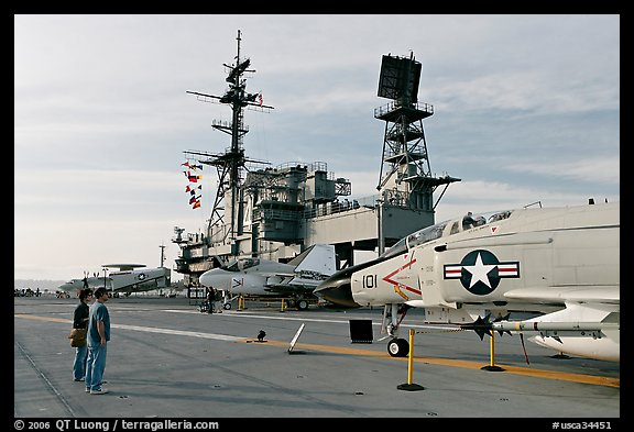 Couple looking at fighter aircraft on the Flight deck of USS Midway. San Diego, California, USA (color)