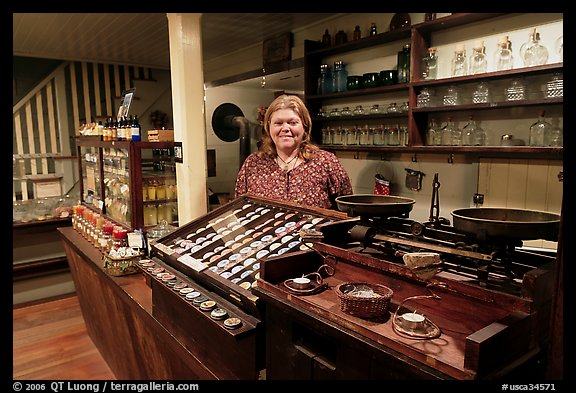 Woman standing behind counter of apothicary store, Old Town. San Diego, California, USA (color)