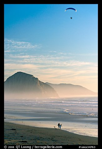 Motorized paraglider, women walking dog, and Morro Rock seen from Cayucos Beach. Morro Bay, USA (color)