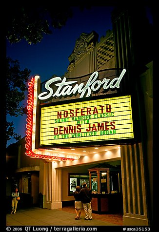 Couple standing in front of Stanford Theatre at night. Palo Alto,  California, USA (color)