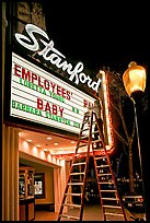 Woman on ladder arranging sign letters, Stanford Theater. Palo Alto,  California, USA (color)