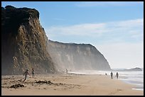 People strolling and playing below cliffs, Scott Creek Beach. California, USA ( color)