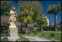 Statue, palm trees, and mission, Santa Clara University. Santa Clara,  California, USA