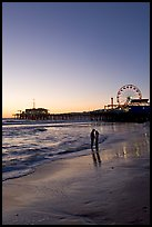 Couple standing on the beach at sunset, with pier and Ferris Wheel behind. Santa Monica, Los Angeles, California, USA (color)