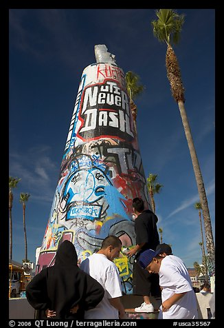 Young men decorating a cone on the beach. Venice, Los Angeles, California, USA (color)