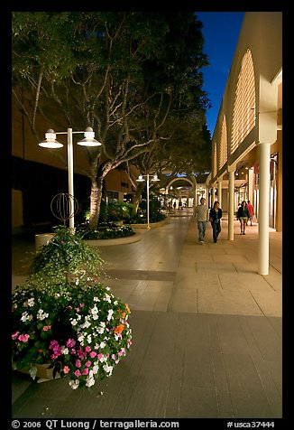 Couple walking by stores and flowers, Stanford Shopping Center. Stanford University, California, USA (color)