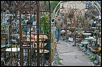 Man browsing in colorful outdoor antique display. Half Moon Bay, California, USA (color)