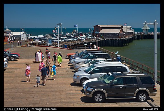 People drapped with colorful towels walking on wharf. Santa Barbara, California, USA (color)