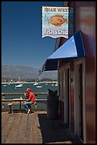 Man eating on wharf next to Fish and Chips restaurant. Santa Barbara, California, USA
