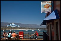 People eating with yachts and beach in background. Santa Barbara, California, USA