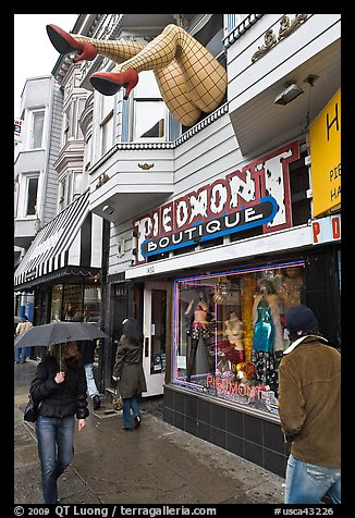 Woman passing with unbrella below giant legs. San Francisco, California, USA (color)