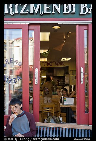 Man biting pizza outside pizzaria, Haight-Ashbury district. San Francisco, California, USA (color)