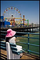 Woman sitting on bench with pink hat and ferris wheel. Santa Monica, Los Angeles, California, USA (color)