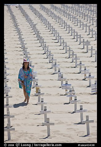 Girl wrapped in towel walking amongst crosses on beach. Santa Monica, Los Angeles, California, USA (color)
