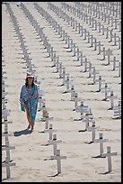 Girl wrapped in towel walking amongst crosses on beach. Santa Monica, Los Angeles, California, USA ( color)