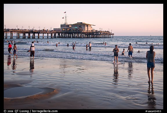Beachgoers near Santa Monica Pier reflected in wet sand, sunset. Santa Monica, Los Angeles, California, USA (color)