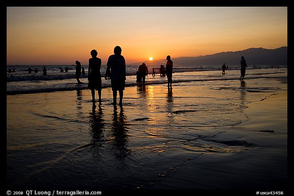 People and reflections on beach at sunset, Santa Monica Beach. Santa Monica, Los Angeles, California, USA (color)