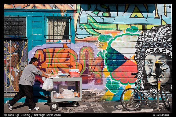 Man pushes vending cart pass mural and bicycle, Mission District. San Francisco, California, USA (color)