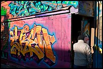 Man opening door of painted garage, Mission District. San Francisco, California, USA ( color)