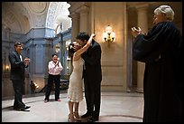 Just married couple kissing, witness and officiant applauding, City Hall. San Francisco, California, USA (color)