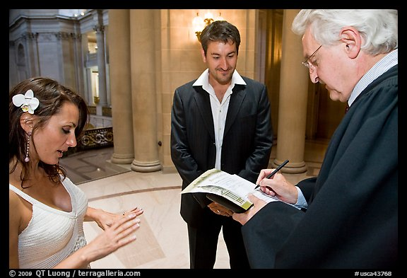 Officiant signing marriage papers as bride looks at ring on finger, City Hall. San Francisco, California, USA (color)