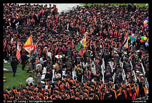 Academic flags exit amongst crow of graduates after commencement ceremony. Stanford University, California, USA (color)