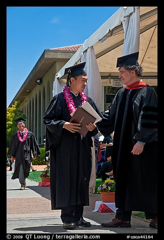 Graduate wearing lei presented with diploma. Stanford University, California, USA (color)