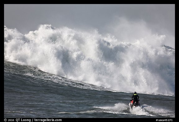 Jet ski dwarfed by huge breaking wave. Half Moon Bay, California, USA (color)