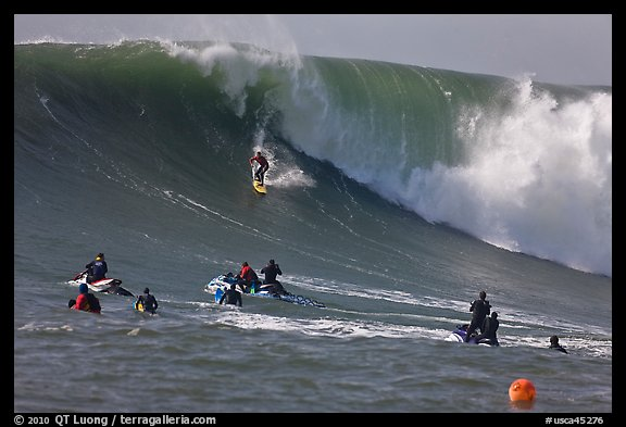 Surfer down huge wall of water observed from jet skis. Half Moon Bay, California, USA (color)