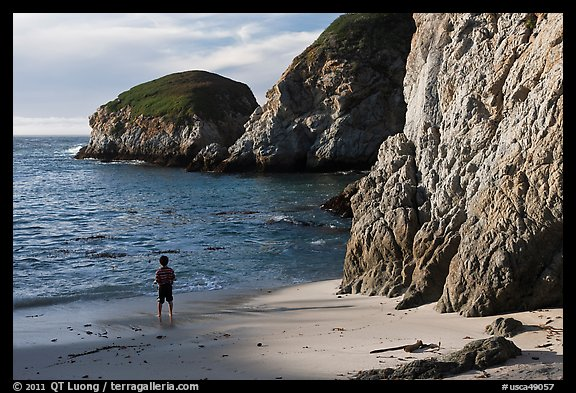 Boy standing at the base of bluff, China Cove. Point Lobos State Preserve, California, USA (color)