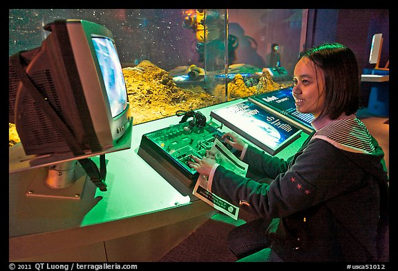 Woman controls robot, Tech Museum. San Jose, California, USA (color)