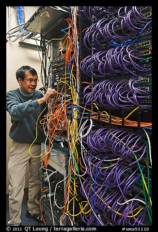 Man with tangle of wires in server room. Menlo Park,  California, USA (color)