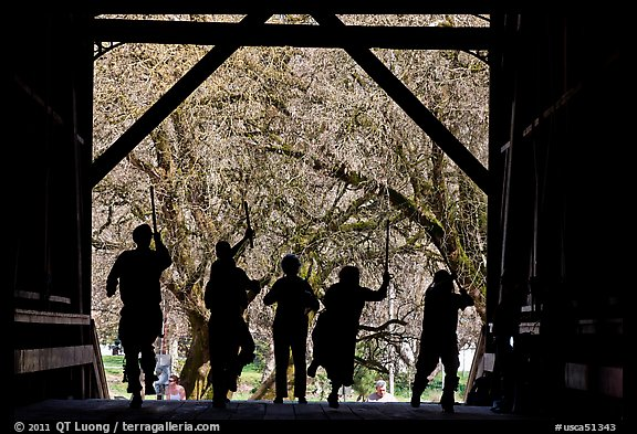 Silhouettes of dancers with sticks inside covered bridge, Felton. California, USA (color)