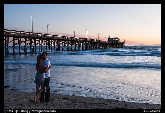 Couple embracing in front of Newport Pier. Newport Beach, Orange County, California, USA (color)