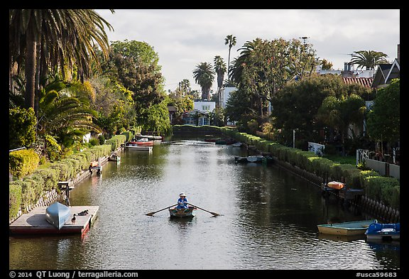 Woman rowing in canal. Venice, Los Angeles, California, USA (color)