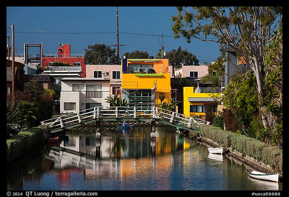 Rower under bridge next to colorful houses. Venice, Los Angeles, California, USA (color)