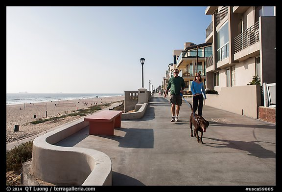 Couple walking dog on beachfront promenade, Manhattan Beach. Los Angeles, California, USA (color)