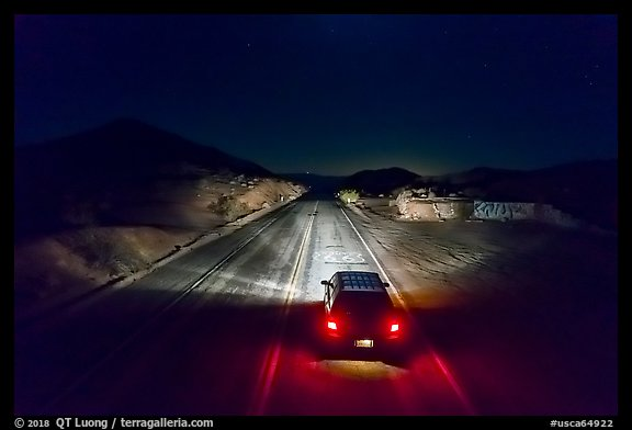Aerial view of car shining headlights on highway 66 maker at night. Mojave Trails National Monument, California, USA (color)