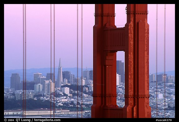 City through cables and pilars of Golden Gate bridge, dusk. San Francisco, California, USA (color)