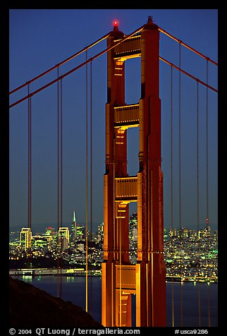 The city seen through the cables and pilars of the Golden Gate bridge, night. San Francisco, California, USA (color)