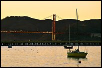 Sailboat in the Marina, with Golden Gate Bridge at sunset in the background. San Francisco, California, USA