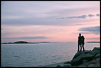 Couple standing on rock and Atlantic Ocean at sunset, Westbrook. Connecticut, USA (color)