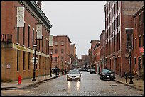 Downtown street lined with brick buildings in the rain, Lowell. Massachussets, USA (color)