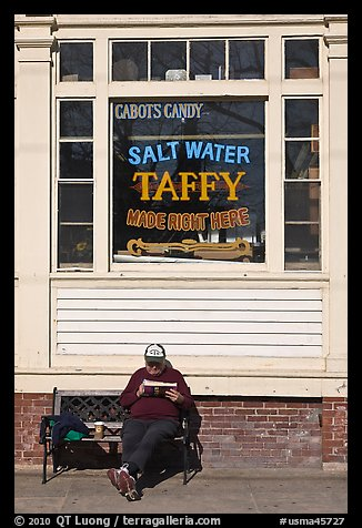 Man reading in front of Salt Water taffy store, Provincetown. Cape Cod, Massachussets, USA (color)