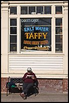 Man reading in front of Salt Water taffy store, Provincetown. Cape Cod, Massachussets, USA ( color)