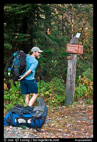 Backpacker shouldering pack at trailhead. Maine, USA (color)
