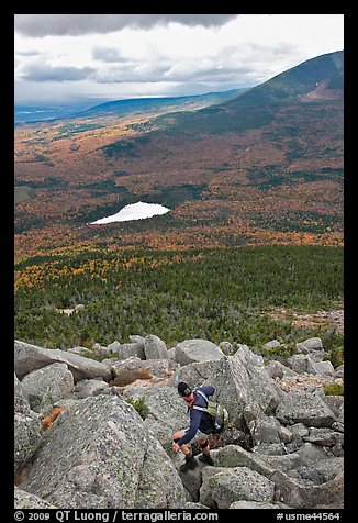 Hiker descends from summit amongst boulders above treeline. Baxter State Park, Maine, USA (color)