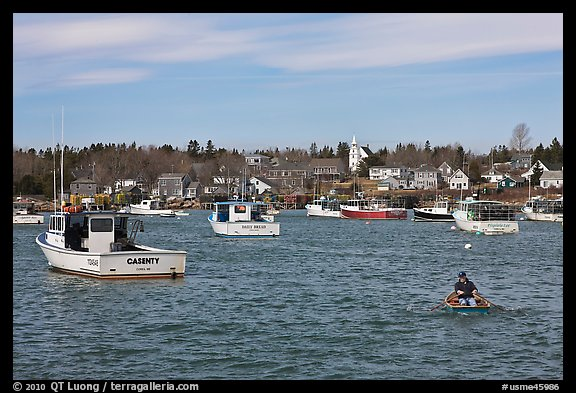 Man paddling to board lobster boat. Corea, Maine, USA (color)